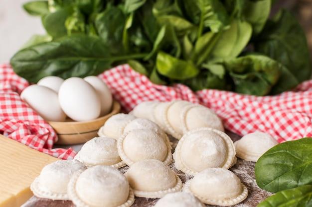 Primer plano de raviolis crudos circulares con espinacas y huevos