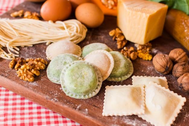 Primer plano de raviolis crudos con ingredientes en tabla de cortar de madera