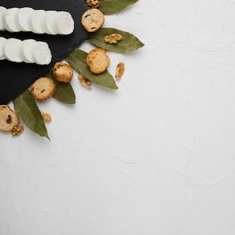 Primer plano de la rebanada de queso de cabra en pizarra negra con rebanada de pan; nogal y hojas de laurel