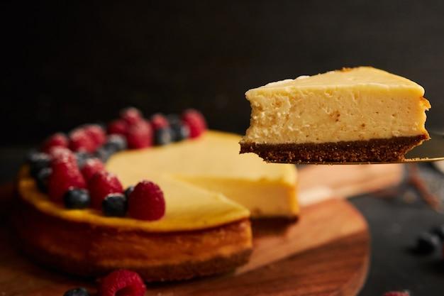 Primer plano de una rebanada de tarta de queso con la tarta con bayas en la parte superior