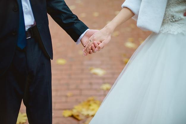 Primer plano de recién casados cogidos de la mano y mostrando sus anillos de boda
