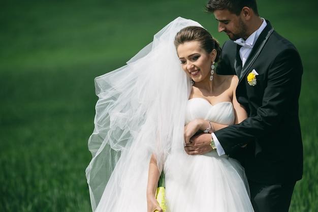 Primer plano de recién casados paseando en el césped