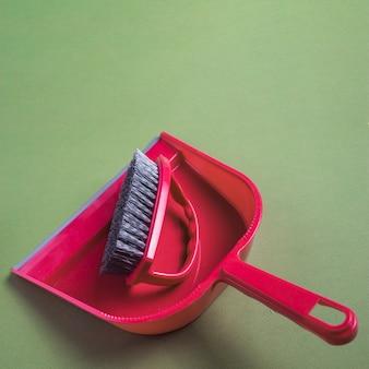 Primer plano de recogedor y cepillo rojo