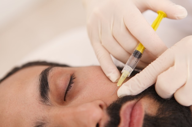 Primer plano recortado de una esteticista inyectando relleno en las arrugas de un cliente masculino