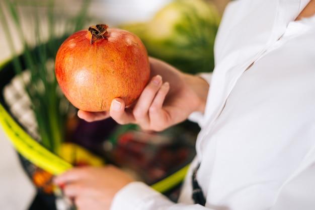 Primer plano recortado de manos femeninas del cliente irreconocible sosteniendo la granada en la tienda de comestibles