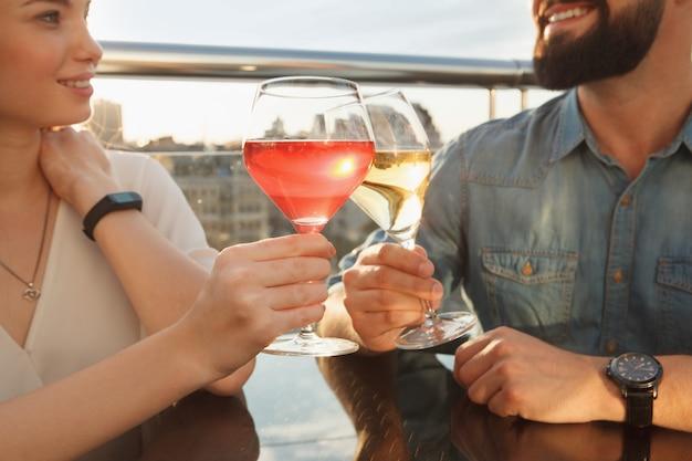 Primer plano recortado de una pareja feliz tintineando copas de vino al atardecer