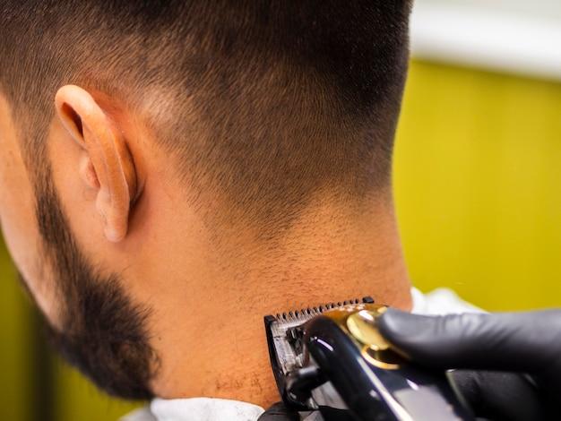 Primer plano de la recortadora en la parte posterior de la cabeza del cliente
