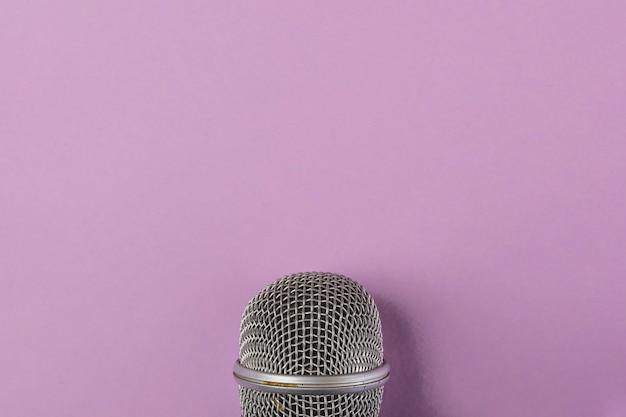 Primer plano de rejilla de acero del micrófono sobre fondo morado