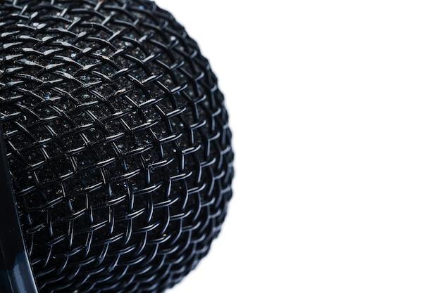 Primer plano de la rejilla del micrófono sobre un fondo blanco.