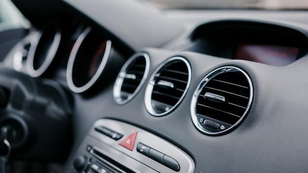 Primer plano de la rejilla de ventilación en el coche. botón de emergencia rojo en el tablero de un automóvil.