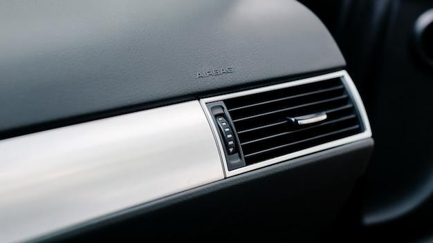 Primer plano de la rejilla de ventilación en el coche. icono de airbag en el panel del vehículo.