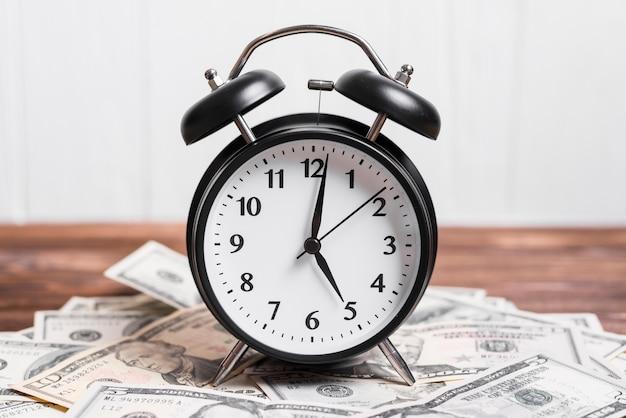 Primer plano de un reloj de alarma en billetes