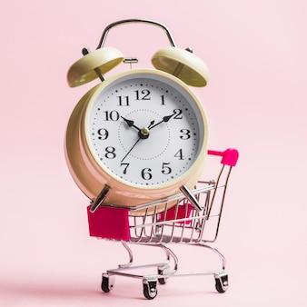 Primer plano de un reloj de alarma en carro sobre fondo rosa