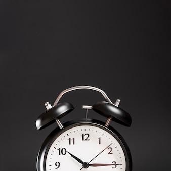 Primer plano de un reloj de alarma contra el fondo negro
