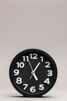 Primer plano de un reloj de alarma negro sobre fondo liso