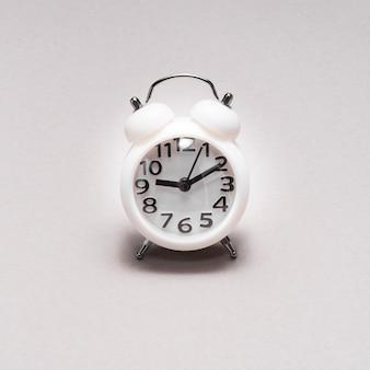 Primer plano de un reloj de alarma sobre fondo liso