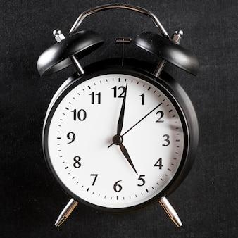 Primer plano de un reloj de alarma sobre fondo negro