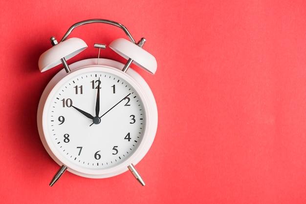 Primer plano de un reloj de alarma sobre fondo rojo