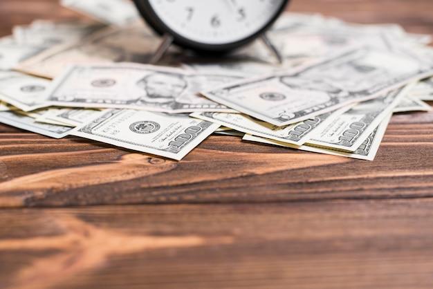 Primer plano del reloj de alarma sobre las notas de la moneda del dólar estadounidense en el escritorio de madera