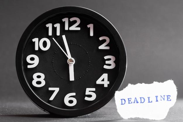 Primer plano de un reloj de alarma con texto de fecha límite