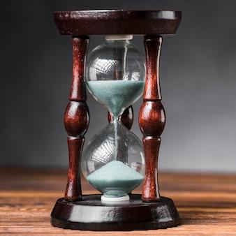 Primer plano de reloj de arena en el escritorio de madera