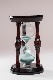 Primer plano de un reloj de arena de madera sobre fondo blanco