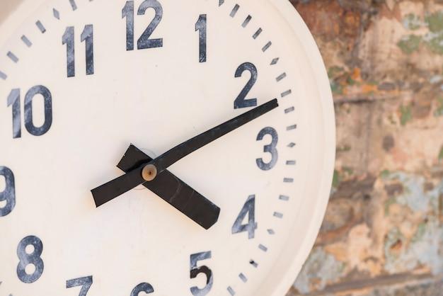 Primer plano de un reloj blanco en la pared desgastada