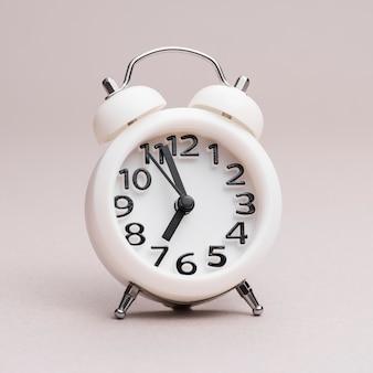 Primer plano de reloj despertador blanco sobre fondo coloreado