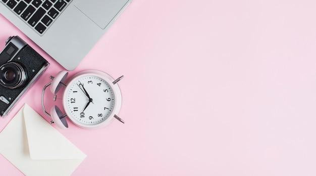 Primer plano de reloj despertador; cámara; sobre y laptop contra fondo rosa