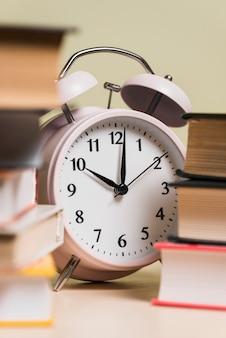 Primer plano de un reloj despertador y libros apilados