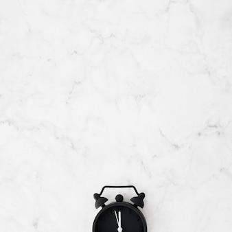 Primer plano de reloj despertador negro sobre el escritorio con textura de mármol