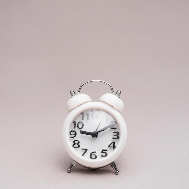 Primer plano de reloj despertador sobre fondo de color