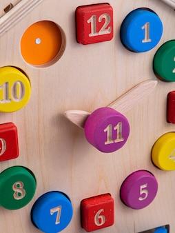 Primer plano de un reloj de madera multicolor en un juguete para niños