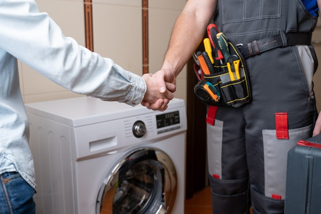 Primer plano de un reparador un apretón de manos con un cliente femenino reparador masculino para la reparación de la lavadora