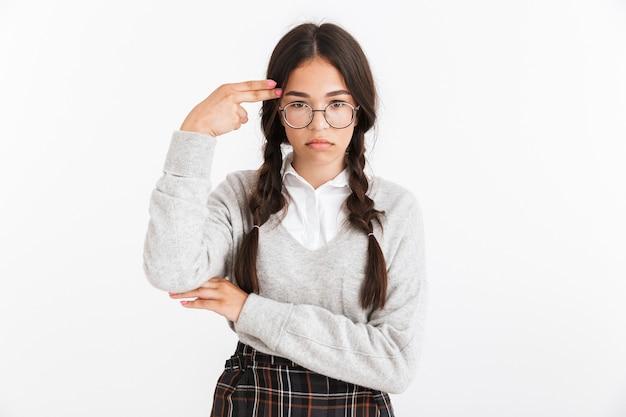 Primer plano retrato de una adolescente deprimida con anteojos y uniforme escolar mostrando gesto de pistola de dedo en su templo aislado sobre la pared blanca
