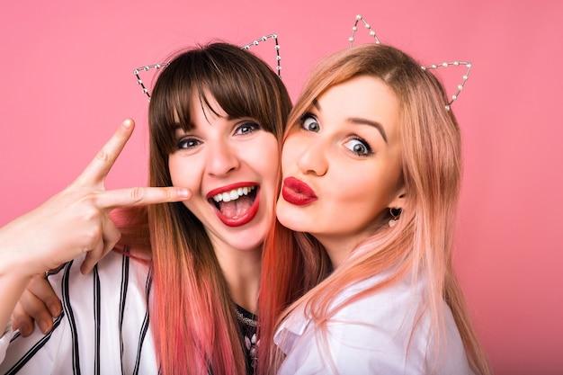 Primer plano retrato de dos mujeres felices con accesorios para el cabello de fiesta de gato, maquillaje brillante, emociones locas divertidas, amigos disfrutando de la fiesta, pared rosa de cerca