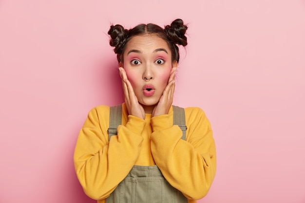 Primer plano retrato de una emotiva chica asiática, toca las mejillas, mira fijamente con los ojos abiertos, retiene el aliento de la emoción, viste una sudadera amarilla y un mono