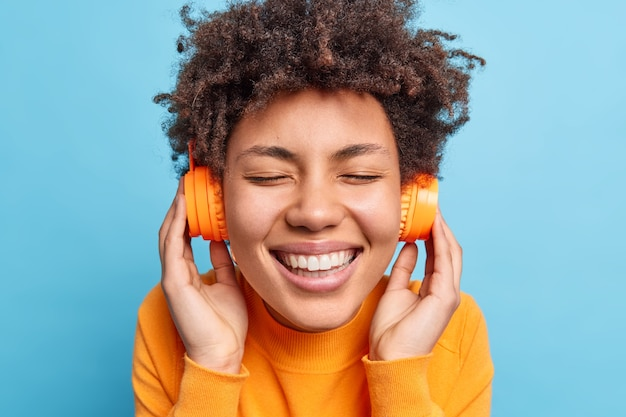 Primer plano retrato de feliz adolescente afroamericana sonríe ampliamente tiene dientes blancos cierra los ojos sueña con algo mientras escucha música agradable a través de auriculares inalámbricos aislados sobre una pared azul