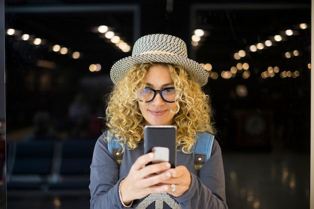Primer plano y retrato de hermosa mujer rizada mirando su teléfono sonriendo y usándolo