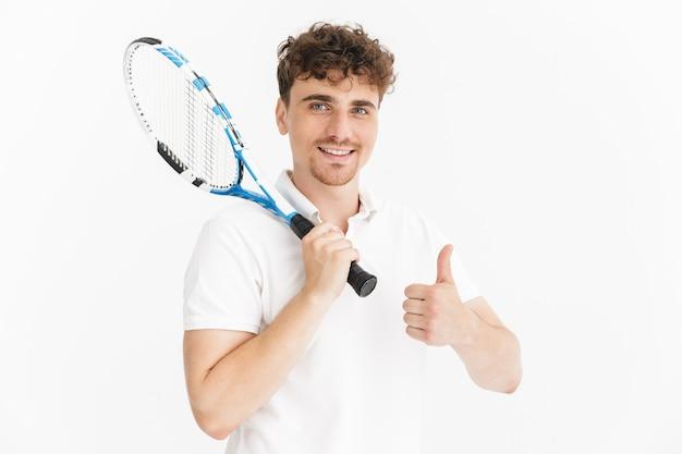Primer plano retrato de hombre feliz en camiseta mostrando el pulgar hacia arriba y sosteniendo la raqueta mientras juega tenis aislado sobre la pared blanca