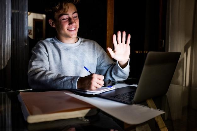 Primer plano y retrato de hombre joven o teeager saludando a alguien en videollamada haciendo tareas y sonriendo mirando la computadora pc o computadora portátil