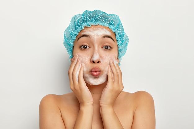 Primer plano retrato de mujer encantadora con labios doblados, aplica jabón en la cara, lava la piel para lucir fresca y limpia, se para con el cuerpo desnudo, mima la cara