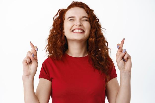 Primer plano retrato de mujer esperanzada y emocionada sonriendo, de pie con los dedos cruzados y pidiendo deseos, rezando por el sueño hecho realidad, suplicando, de pie contra la pared blanca