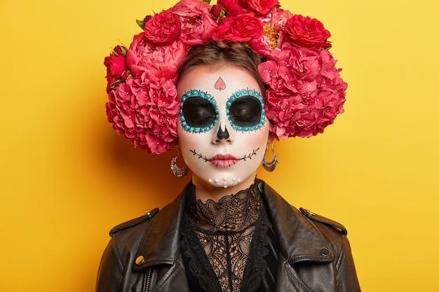 Primer plano retrato de mujer joven demuestra arte facial, usa maquillaje profesional, corona y chaqueta se prepara para la fiesta de disfraces de halloween, mantiene los ojos cerrados