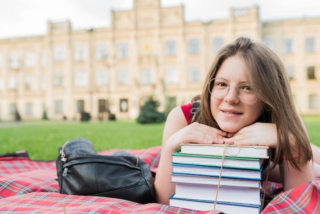 Primer plano retrato de niña de la escuela tendido en manta con libros