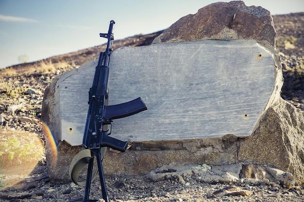 Primer plano de rifle de asalto kalashnikov sobre un fondo de losas de granito