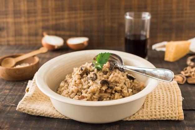 Primer plano de risotto de setas en un tazón blanco con una cuchara en la servilleta sobre la mesa
