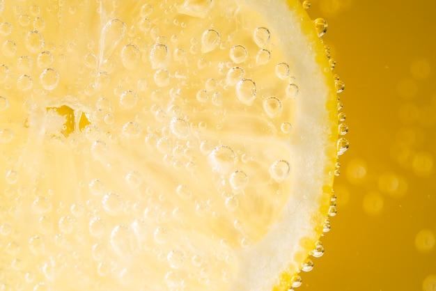 Primer plano de rodaja de limón con gotas de agua