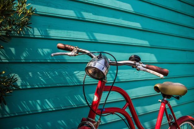 Primer plano rojo de aparcamiento de bicicletas vintage en pared de madera azul con espacio de copia