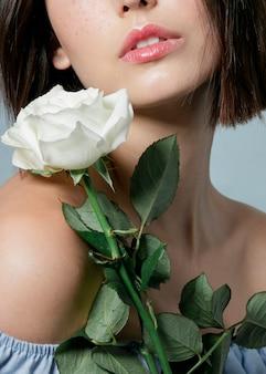 Primer plano de rosa florecida con mujer
